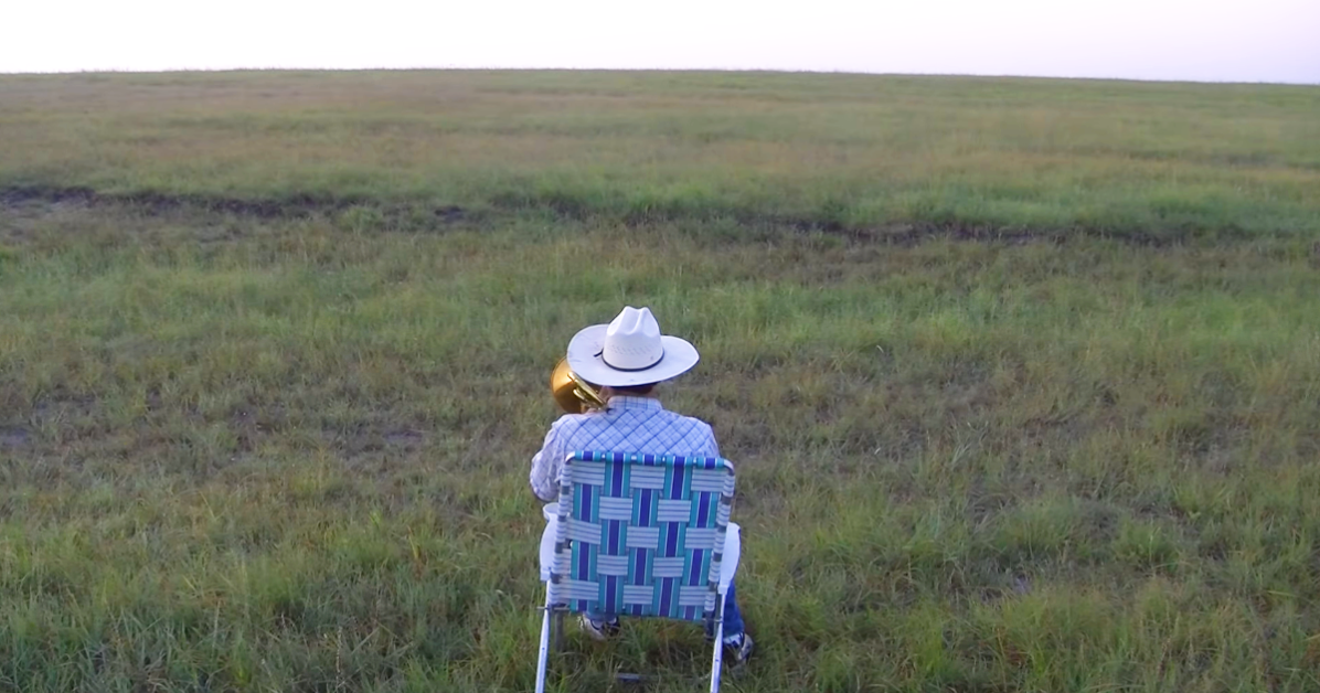 Farmer with trombone in the field, cows come running to the music