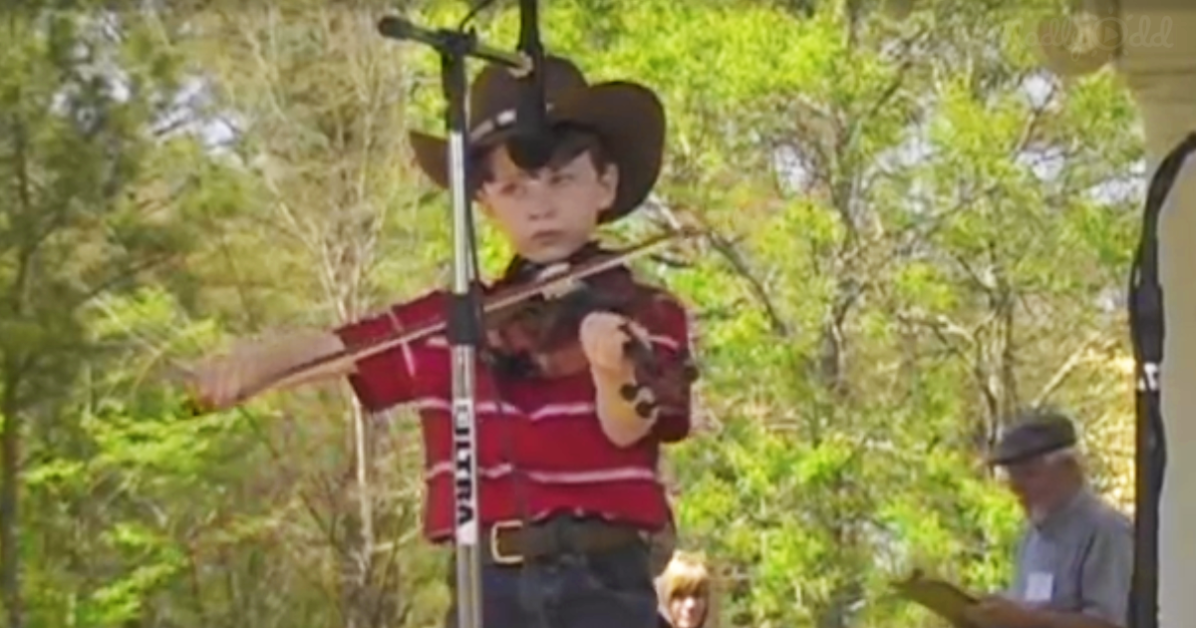 Boy at fair playing fiddle, contest - serious face